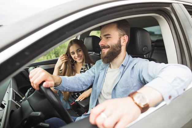 Sorrindo, mulher jovem, olhar, seu, namorado, dirigindo carro Foto gratuita