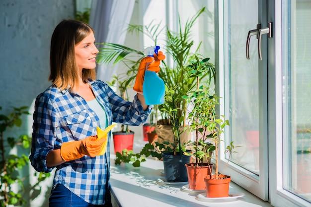 Sorrindo, mulher jovem, pulverização, ligado, vidro janela Foto gratuita