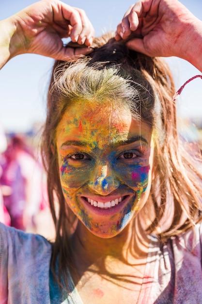 Sorrindo, mulher jovem, rosto, coberto, com, holi, cor, olhando câmera Foto gratuita