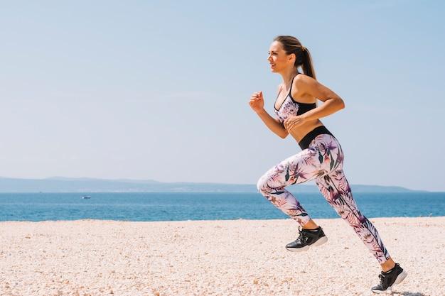 Sorrindo, mulher jovem, sacudindo, perto, a, praia, contra, céu azul Foto gratuita