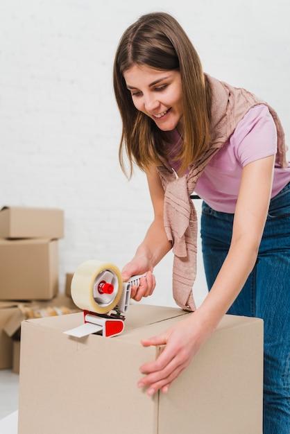 Sorrindo, mulher jovem, segurando, embalagem, máquina, e, selando, caixas cartão, com, fita adesiva Foto gratuita