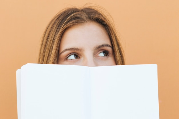 Sorrindo, mulher jovem, segurando, livro branco, em, dela, mão, olhando câmera Foto gratuita