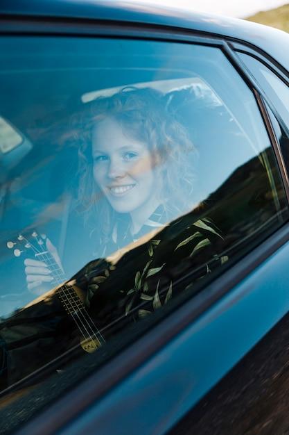 Sorrindo, mulher jovem, sentando, carro Foto gratuita