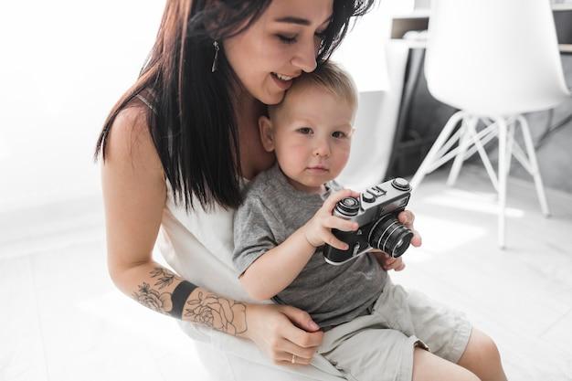 Sorrindo, mulher jovem, sentando, com, dela, filho, segurando câmera, casa Foto gratuita