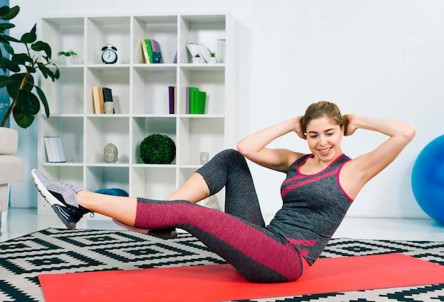 Sorrindo, mulher jovem, sentando, ligado, esteira vermelha exercício, fazendo, relaxante, exercício Foto gratuita