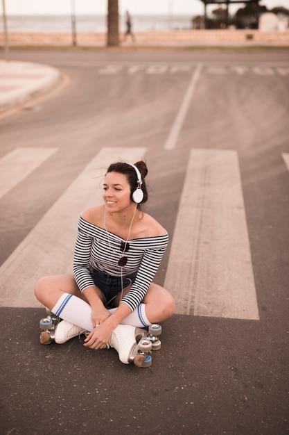 Sorrindo, mulher jovem, sentando, ligado, estrada, desgastar, patim rolo, escutar, música, ligado, headphone Foto gratuita