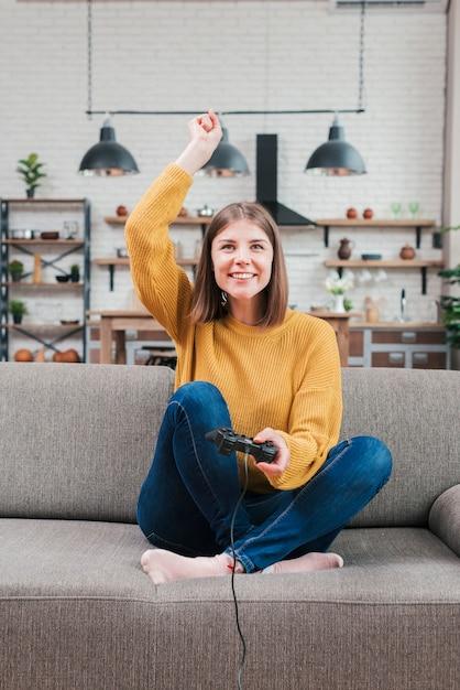Sorrindo, mulher jovem, sentar sofá, alegrando, enquanto, jogando videogame Foto gratuita