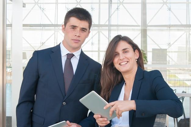 Sorrindo, mulher, mostrando, homem, dados, ligado, tabuleta, eles, olhando câmera Foto gratuita