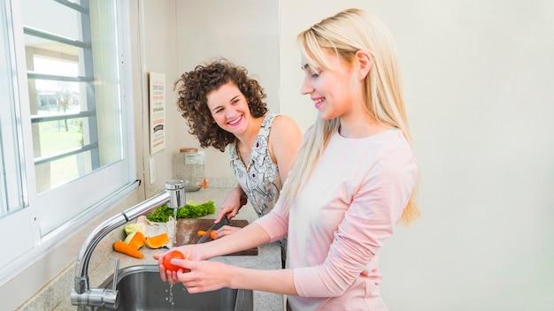 Sorrindo, mulher olha, em, dela, amigo feminino, lavando, tomate, em, a, pia cozinha Foto gratuita