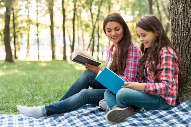 Sorrindo, mulher olha, em, livro, segurando, por, dela, filha, enquanto, sentando, parque Foto gratuita