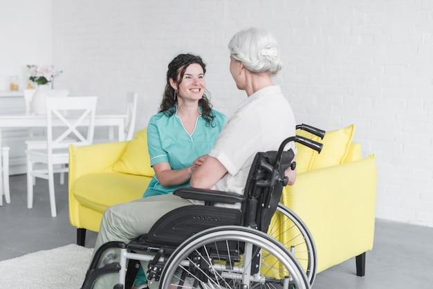 Sorrindo, mulher olha, em, mulher sênior, sentando, ligado, cadeira roda Foto gratuita