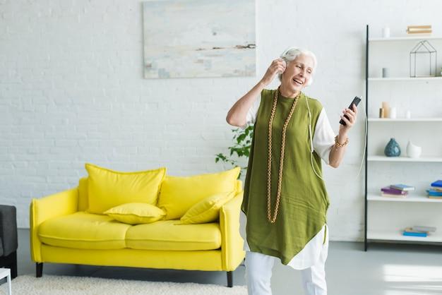 Sorrindo, mulher sênior, escutar música, ligado, auscultadores, através, cellphone Foto gratuita