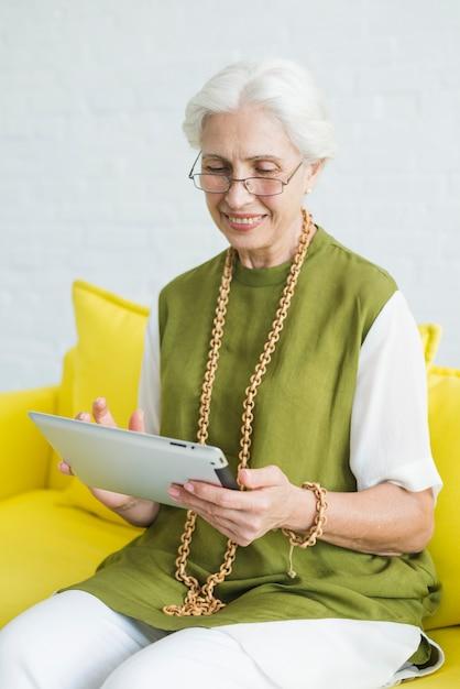 Sorrindo, mulher sênior, navegar, ligado, tablete digital Foto gratuita