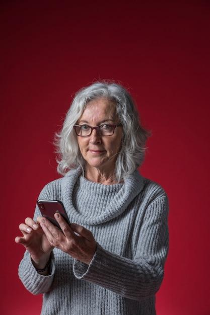 Sorrindo, mulher sênior, segurando, esperto, telefone, em, mão, olhando câmera, contra, experiência colorida Foto gratuita