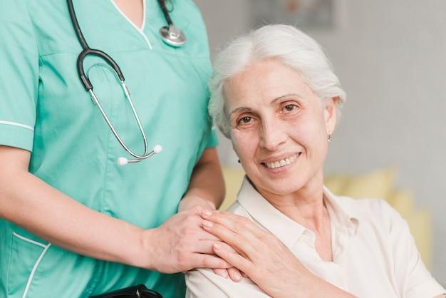 Sorrindo, mulher sênior, toque, enfermeira, mão ombro Foto gratuita