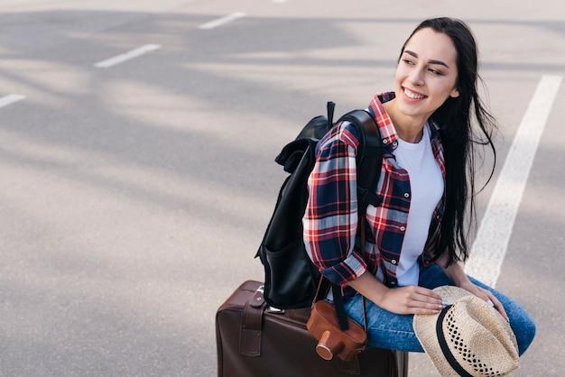Sorrindo, mulher senta-se, bagagem, saco, com, câmera, e, mochila, em, ao ar livre Foto gratuita