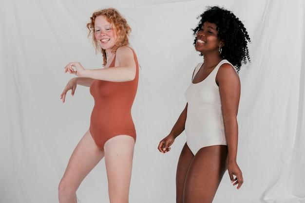 Sorrindo, mulheres jovens, dançar, contra, cinzento, fundo Foto gratuita