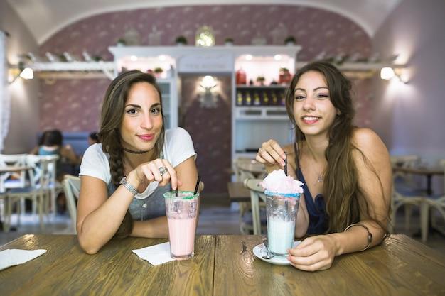Sorrindo, mulheres jovens, sentando, com, óculos, milkshake Foto gratuita