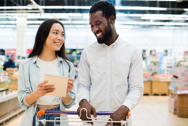 Sorrindo, multiétnico, par, comprando, bens, em, supermercado Foto gratuita