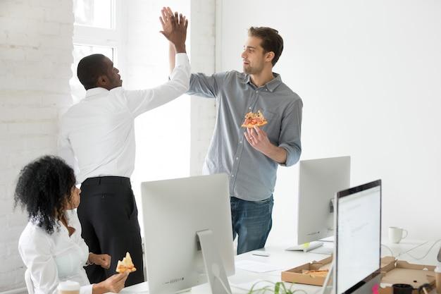 Sorrindo, multiracial, colegas trabalho, dar, alto cinco, comendo pizza, junto, em, escritório Foto gratuita