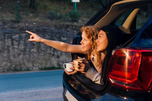 Sorrindo namoradas multiétnicas relaxantes no porta-malas Foto gratuita