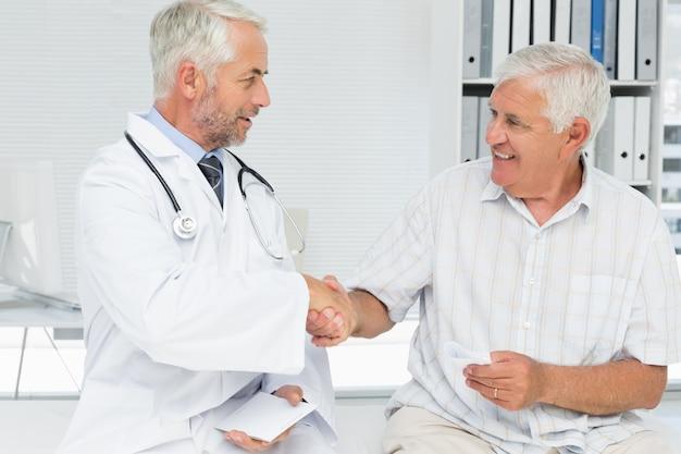 Sorrindo paciente sênior e doutor apertando as mãos Foto Premium