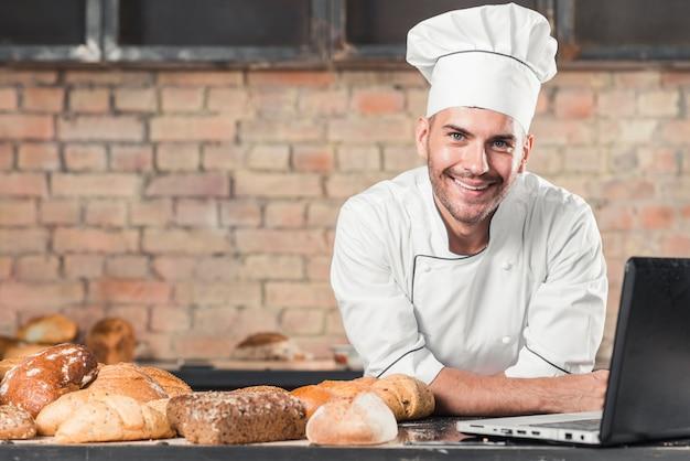 Sorrindo padeiro masculino com diferentes tipos de pães assados e laptop na bancada da cozinha Foto gratuita