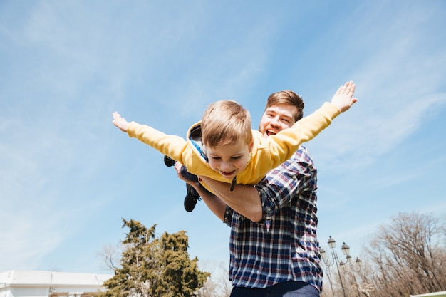 Sorrindo pai barbudo se divertindo com seu filho pequeno Foto gratuita