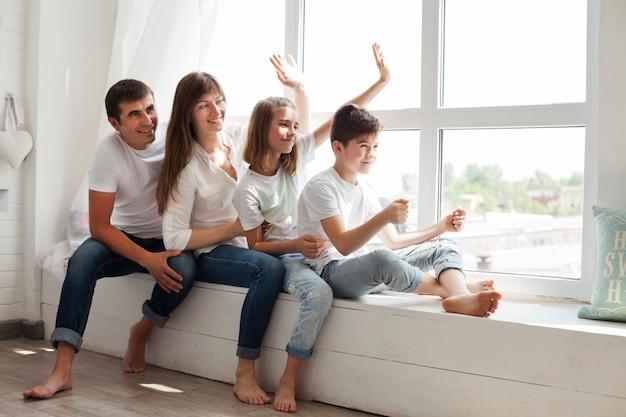 Sorrindo pai brincando com seus filhos, localização perto da janela Foto gratuita