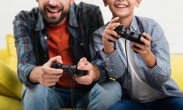 Sorrindo, pai e filho brincando no console Foto gratuita