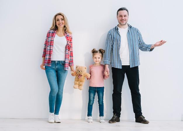 Sorrindo pais com sua filha de pé contra a parede branca Foto gratuita