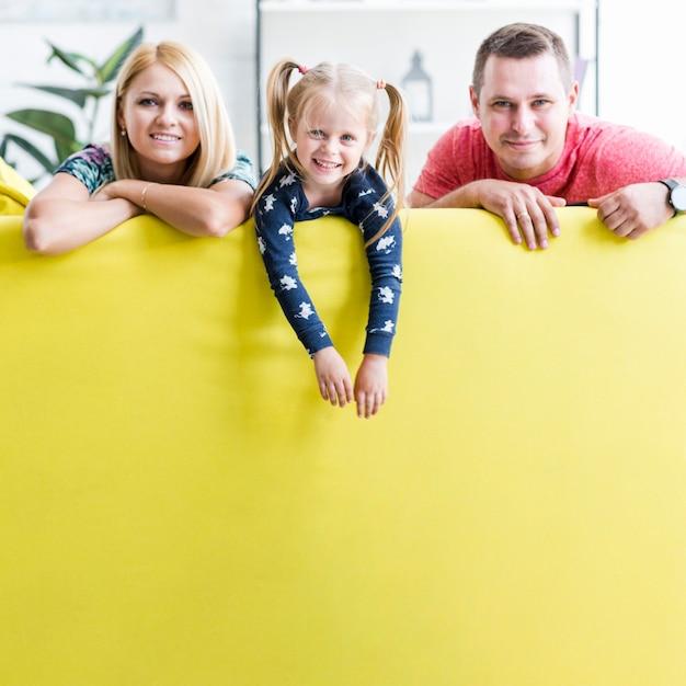 Sorrindo, par, com, criança, sentar sofá Foto gratuita