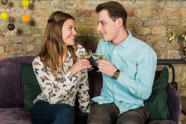 Sorrindo, par jovem, brindar, copos de vinho, em, clube Foto gratuita
