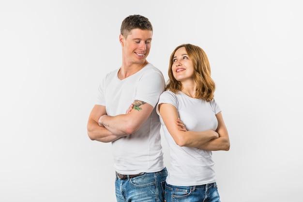 Sorrindo, par jovem, ficar, costas, para, costas, olhando um ao outro, contra, fundo branco Foto gratuita