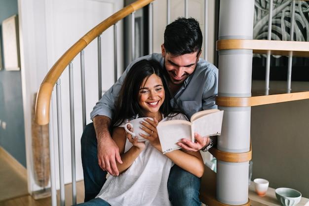 Sorrindo, par jovem, sentando, ligado, escadaria, livro leitura Foto gratuita