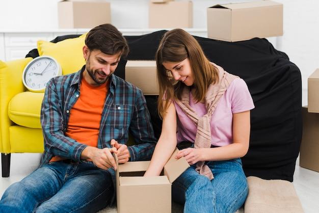 Sorrindo, par jovem, sentando, perto, a, sofá, desembalando caixa, em, casa nova Foto gratuita