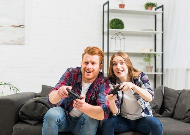 Sorrindo, par jovem, videogame jogando, com, joystick Foto gratuita