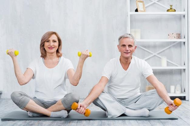 Sorrindo, par, sentando, ligado, esteira yoga, exercitar, com, dumbbells Foto gratuita
