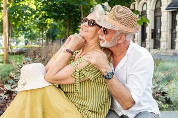 Sorrindo, par velho, sentando um banco Foto gratuita