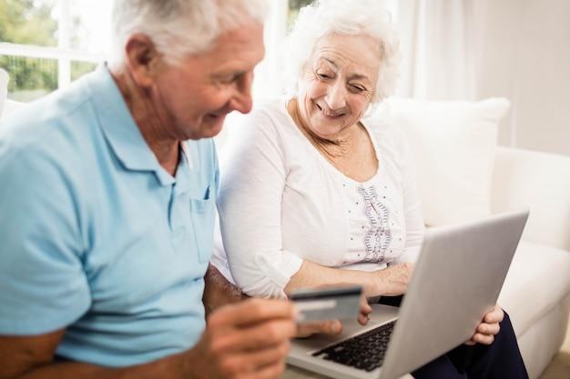 Sorrindo, par velho, usando computador portátil, casa Foto Premium