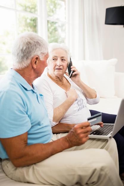 Sorrindo, par velho, usando computador portátil, e, smartphone, casa Foto Premium
