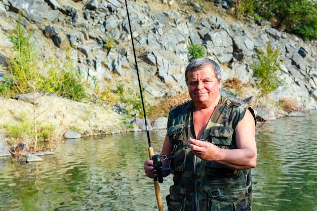 Sorrindo pescador com uma vara de pescar em um lago de montanha Foto Premium