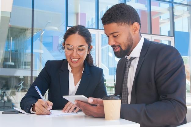 Sorrindo, pessoas negócio, trabalhando, e, usando, tabuleta, em, café ao ar livre Foto gratuita