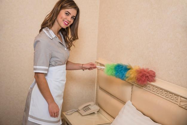 Sorrindo, retrato, de, um, empregada, limpeza, a, poeira, com, macio, pena Foto gratuita