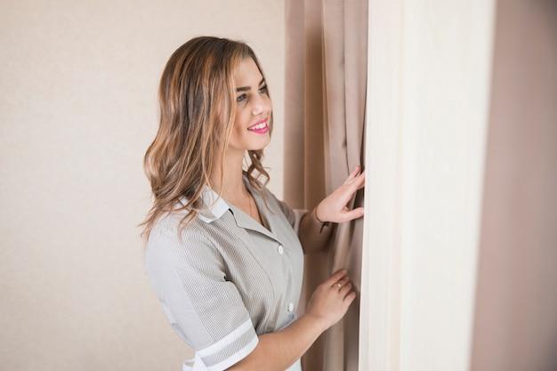 Sorrindo, retrato, de, um, femininas, chambermaid, olhar janela Foto gratuita