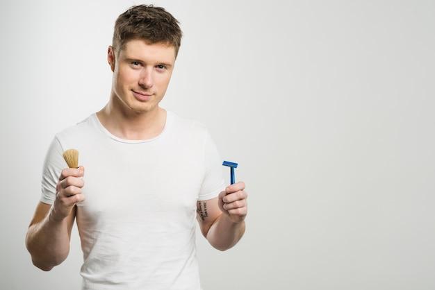 Sorrindo, retrato, de, um, homem jovem, segurando, navalha, e, escova raspando, em, mãos Foto gratuita