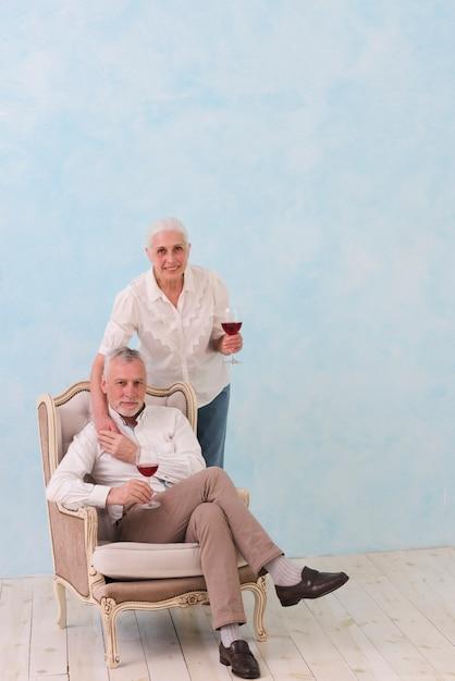 Sorrindo, retrato, de, um, homem sênior, sentando, ligado, cadeira, com, seu, posição mulher, atrás de, segurando, copo vinho Foto gratuita