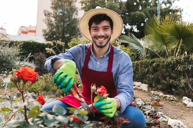 Sorrindo, retrato, de, um, jardineiro masculino, poda, a, flor rosa, com, secateurs Foto gratuita