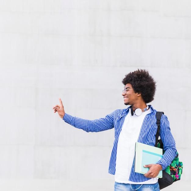 Sorrindo, retrato, de, um, jovem, afro americano jovem, carregar saco, ligado, ombro, e, livros, em, mão, ficar, contra, parede Foto gratuita