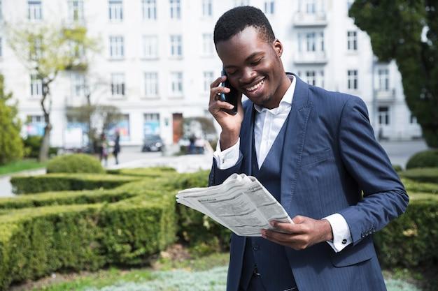 Sorrindo, retrato, de, um, jovem, homem negócios, falando telefone móvel, lendo jornal Foto gratuita